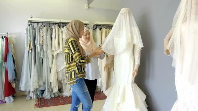 vídeos de stock, filmes e b-roll de noiva de ser está à procura de um vestido de noiva com sua amiga - vestuário modesto