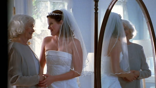 A bride turns from a mirror to hug her mother.