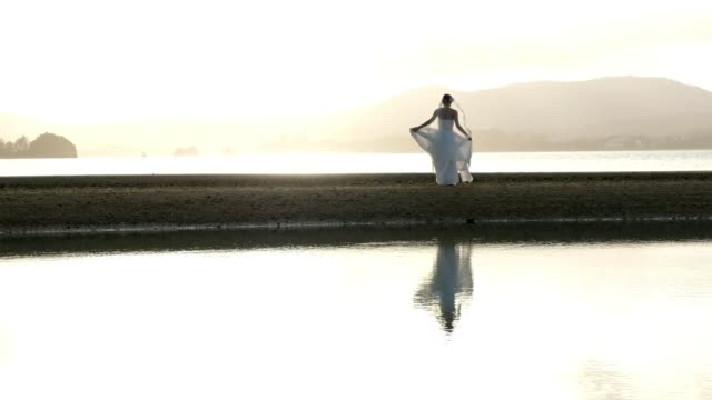 a bride walking on the beach. - honeymoon stock videos and b-roll footage