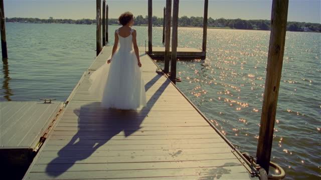 MS, bride walking on wooden pier on lake, rear view, USA, Pennsylvania, Solebury