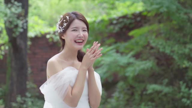 vídeos de stock, filmes e b-roll de a bride who smiling brightly an outdoor wedding studio - mãos cobrindo boca