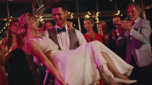 bridegroom carrying bride while dancing in wedding - marito video stock e b–roll