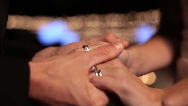 HANDHELD CLOSE UP bride's hand puts wedding ring on groom's finger