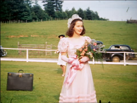 vídeos de stock, filmes e b-roll de 1940 portrait bridesmaid holding flowers posing for camera outdoors / maplewood, nj / home movie - bridesmaid