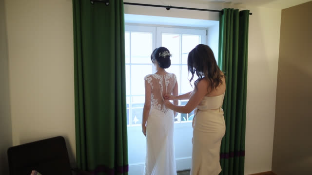 bridesmaid preparing bride for the wedding. bridesmaid buttoning wedding dress - dress stock videos & royalty-free footage