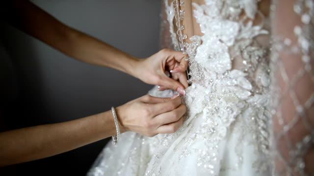 結婚式のために花嫁を準備するブライドメイド。ブライドメイドボタンウェディングドレス - ウェディングドレス点の映像素材/bロール