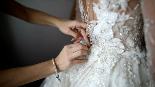 bridesmaid preparing bride for the wedding. bridesmaid buttoning wedding dress - abito da sposa video stock e b–roll