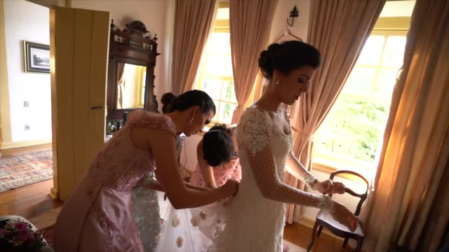 bridesmaids (mother and sister) helping bride getting dressed for the wedding ceremony - christianity stock videos & royalty-free footage