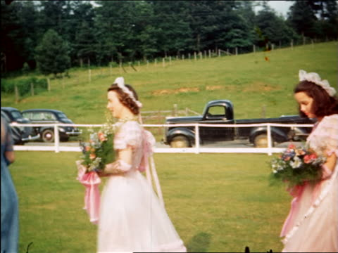 vídeos de stock, filmes e b-roll de 1940 bridesmaids + man in tuxedo walk past camera outdoors / maplewood, nj / home movie - bridesmaid