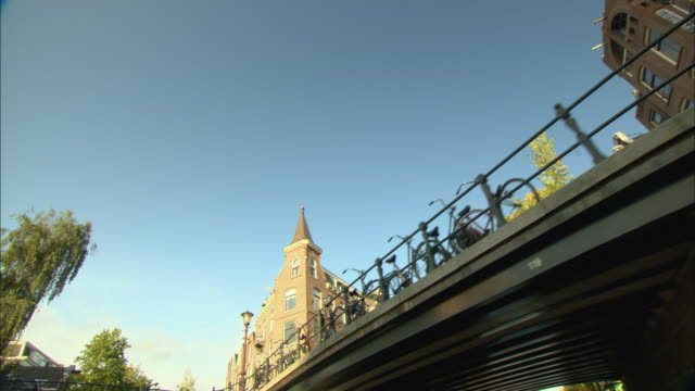 POV Bridge and old apartment buildings seen from boat moving down canal / Amsterdam, Holland