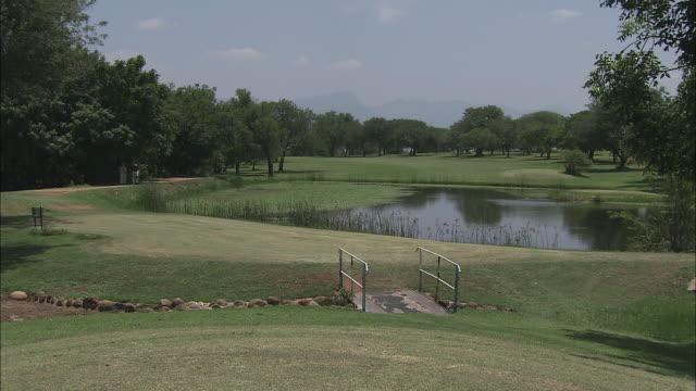 vídeos de stock, filmes e b-roll de a bridge crosses the golf green near a water hazard where golfers play. - obstáculo de água
