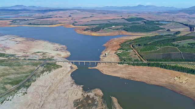bridge crossing over the ever receding water levels of the theewaterskloof dam in a drought - drought stock videos & royalty-free footage