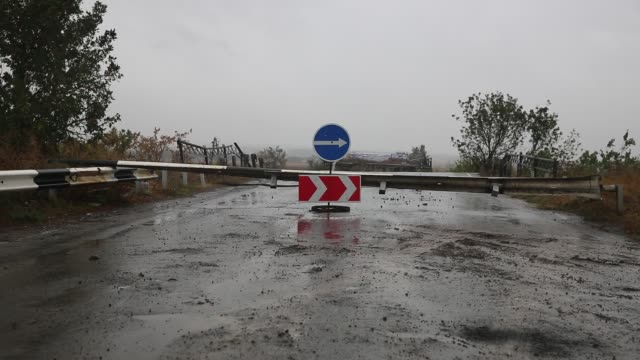 bridge is destroyed by explosive device on road leading into semyonovka. semyonovka, which is still on the war front, was heavily damaged in a battle... - war stock-videos und b-roll-filmmaterial