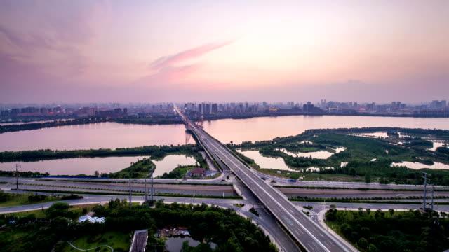 ブリッジ湖日没に、中国の都市、微速度撮影、夕暮れから夜 - 列車の車両点の映像素材/bロール