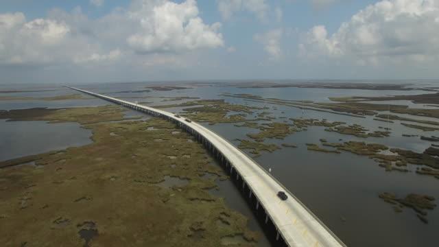 Bridge reveal around swamp - Drone Aerial 4K Lake Pontchartrain CausewayGrand Isle Louisiana coast Mississippi river bridge and barge everglades, gulf delta, with wildlife 4K Transportation