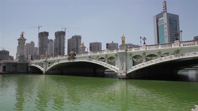 a bridge spans the hai river in downtown tianjin, china. - hai river stock videos & royalty-free footage