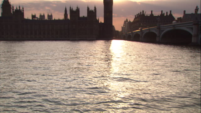a bridge spans the river thames to the house of parliament and big ben. - parliament building stock-videos und b-roll-filmmaterial
