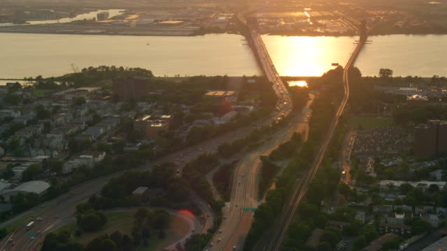 LONG AERIAL bridge with traffic and railroad bridge over water at sunset