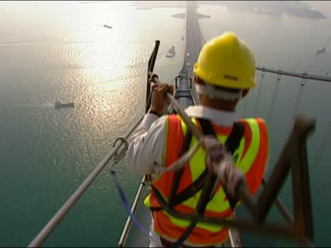 cu bridge worker wearing safety harness walking on top of bridge - safety harness stock videos & royalty-free footage