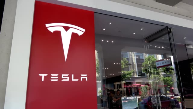 brief clip panning from logo on facade of tesla motors store in the silicon valley san jose california to people exiting the store june 7 2018 - facade stock videos & royalty-free footage