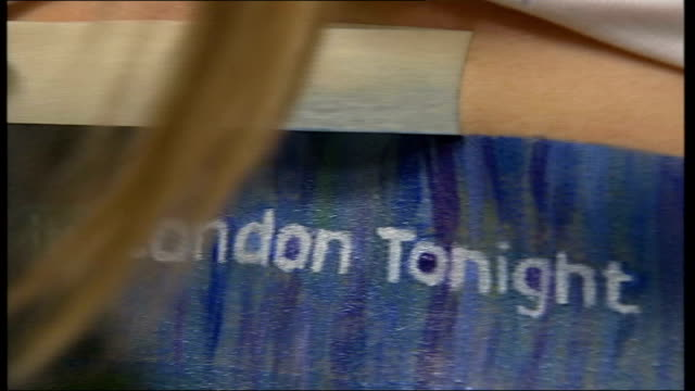 briefcases to be used for advertisements tx int 'london tonight' advert being painted on woman's stomach ext 'london tonight' advertisement on belly... - itv london tonight点の映像素材/bロール