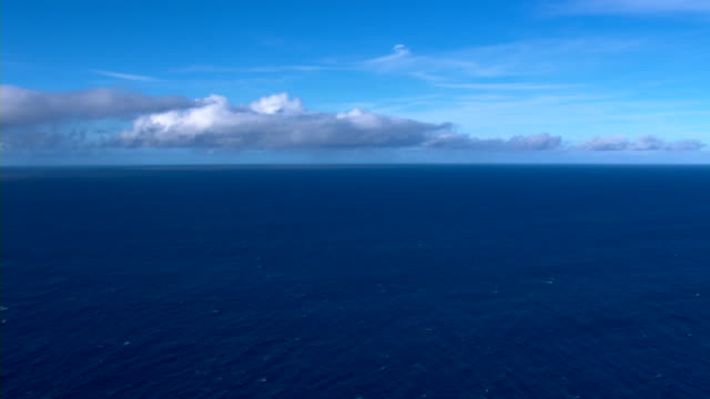 A bright blue sky overlooks the vivid aquamarine waters of the Pacific Ocean off the coast of Maui.