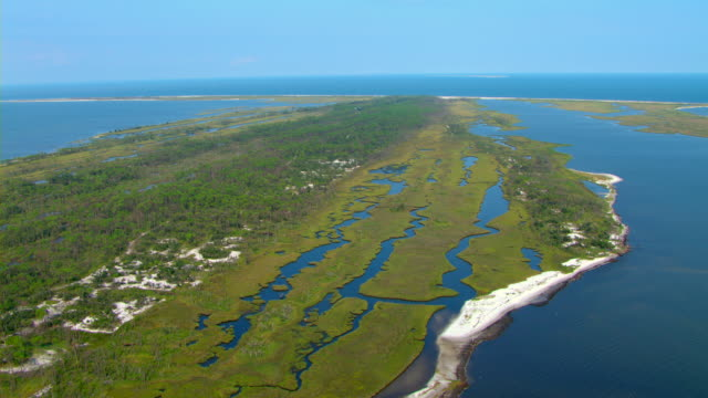 Bright blue water surrounds the grassy coastline of Gulf Islands National Seashore in Mississippi.