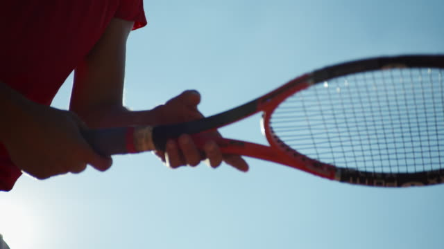 bright lens flare and bright blue sky as man twirls tennis racket in slow motion, shot from below - tennis stock videos & royalty-free footage