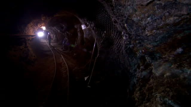 a bright light illuminates a mining tunnel where a geologist walks past. - mining stock videos & royalty-free footage
