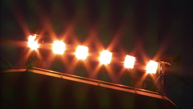 vídeos de stock e filmes b-roll de bright lights and security cameras, belfast international airport, northern ireland - iluminado por holofote