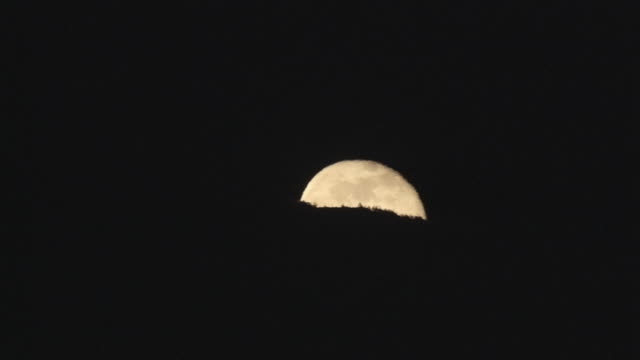 vidéos et rushes de ws bright moon slowly rising above a hill in a nearly black sky - au loin