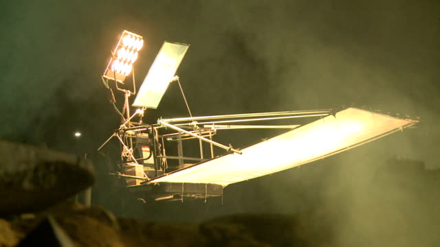 bright movie set lights crane and move through the special effects fog at night - movie set stock videos and b-roll footage