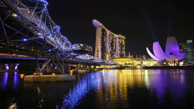 bright, neon lights and lasers illuminate heiix bridge and the buildings of the marina bay sands. - marina bay sands stock videos and b-roll footage