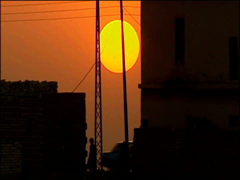 Bright orange sun sets over silhouetted buildings people and river