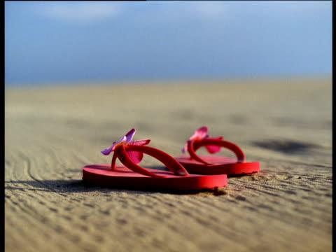 bright pink flip flops on empty sandy beach under blue sky - サンダル点の映像素材/bロール