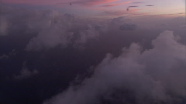 bright pink sunlight shines over the top of a thin layer of wispy white clouds. - wispy stock videos & royalty-free footage
