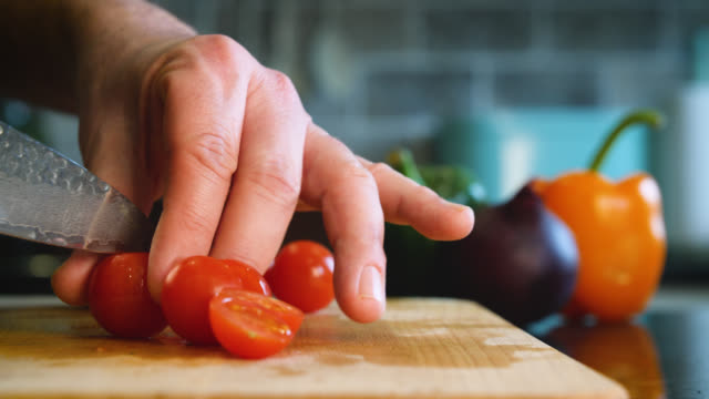 bright red cherry tomatoes are halved with a knife - オレンジピーマン点の映像素材/bロール