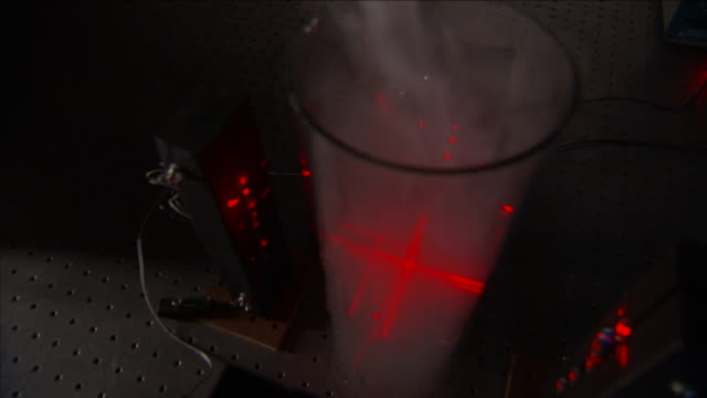 a bright red light illuminates a beaker as a vapor is poured in. - neutron stock-videos und b-roll-filmmaterial