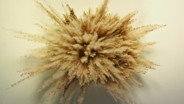vidéos et rushes de bright skin colored powder foundation exploding towards camera in close up and super slow-motion - beige