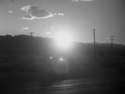 bright sun beginning to set above spring mountain range mountains utility telephone poles in silhouette car passing through fg - 1952 stock videos & royalty-free footage