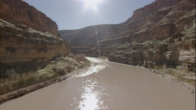 A bright sun shines above a muddy river that flows through a canyon. Available in HD.