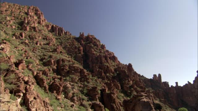 vidéos et rushes de a bright sun shines above craggy rock formations. - piton rocheux