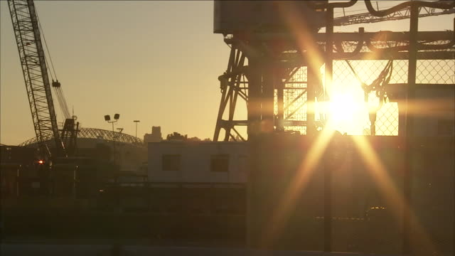a bright sun shines over a busy shipyard. - docker stock videos & royalty-free footage