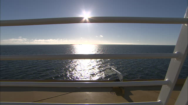 A bright sun shines over the ocean as a cruise ship sails past.