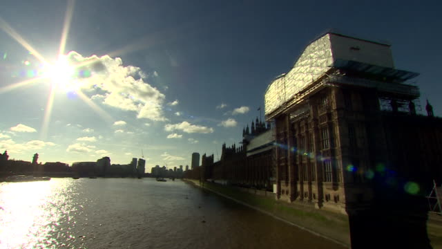 bright sun shining in blue sky over river thames and houses of parliament - illuminated stock videos & royalty-free footage