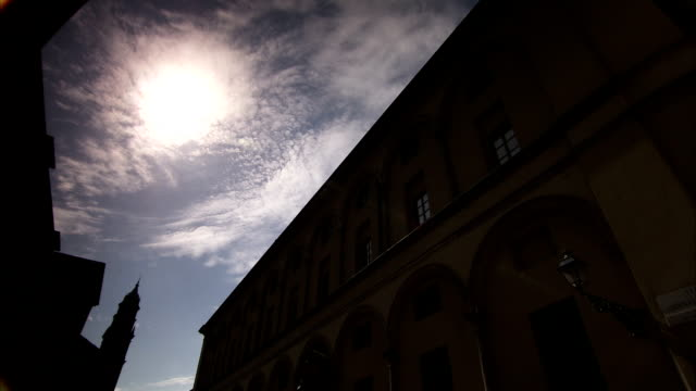 a bright sun silhouettes imposing buildings of the bishop's palace of parma. available in hd. - parmigiano video stock e b–roll