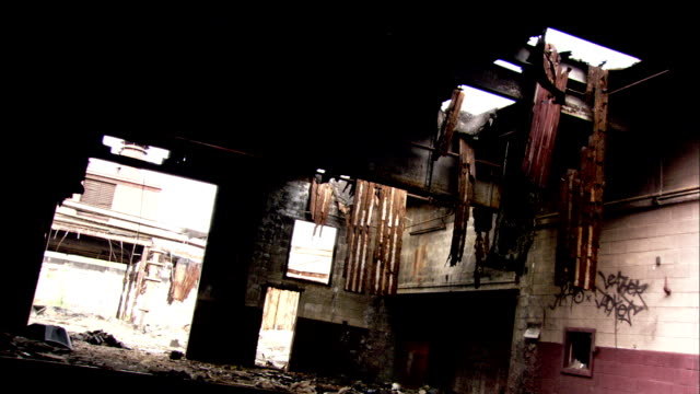 Bright sunlight fills the inside of a derelict warehouse. Available in HD.