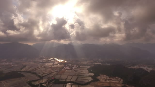 Bright white light and crepuscular rays shone through clouds above the rural countryside landscape in Thailand