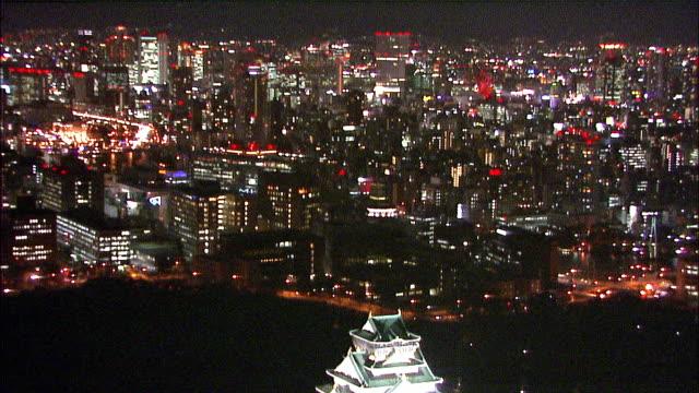 Bright white lights illuminate Osaka Castle in Naka-no-Shima, Japan. Aerial Shot