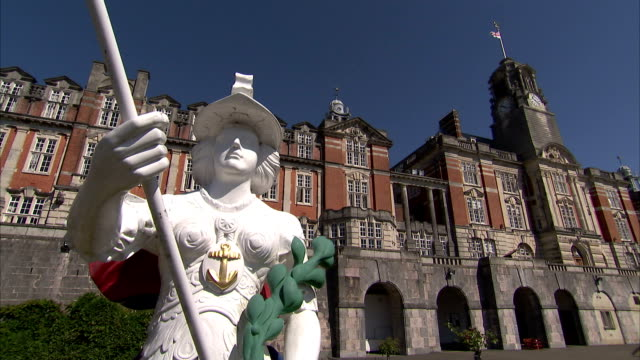 stockvideo's en b-roll-footage met a bright white statue of a man holding a rod stands in front of a building on the campus of britannia royal naval college. available in hd. - devon